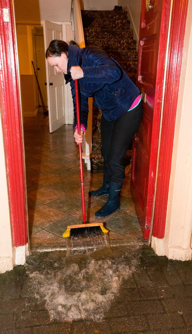 Pauline Delaney sweeps water from her house during the flooding in Mountmellick, Co. Laois. Photo: Tony Gavin 22/11/2017