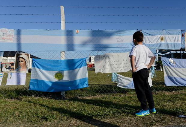 A boy looks at signs and flags in support of the crew of the missing submarine ARA San Martin, that hang from the fence of the Mar del Plata Naval Base, in Argentina, Wednesday, Nov. 22, 2017. The families of the 44 crew members aboard a submarine that has been lost in the South Atlantic for seven days are growing increasingly distressed as experts say that the crew might be reaching a critical period of low oxygen. (AP Photo/Marina Devo)