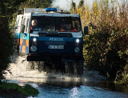 An all-terrain vehicle of the Civil Defence brings food and people around the flooded areas of Mountmellick. Photo: Kevin Byrne