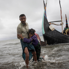 A Rohingya man carries an elderly woman, after the wooden boat they were travelling on from Myanmar, which can be seen in the background, crashed into the shore and tipped everyone out in September in Dakhinpara, Bangladesh. Photo: Getty Images