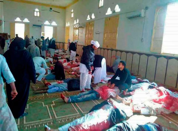 Egyptians walk past bodies following a gun and bombing attack at the Rawda mosque, roughly 40 kilometres west of the North Sinai capital of El-Arish. A bomb explosion ripped through the mosque before gunmen opened fire on the worshippers gathered for weekly Friday prayers, officials said. Photo: Getty Images