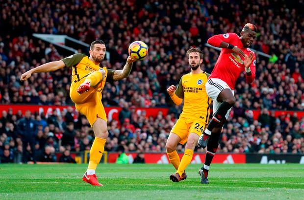 Manchester United's Paul Pogba (right) flinches as Brighton & Hove Albion's Shane Duffy intercepts