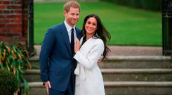 Britain's Prince Harry and his fiancée US actress Meghan Markle pose for a photograph in the Sunken Garden at Kensington Palace in west London on November 27, 2017, following the announcement of their engagement