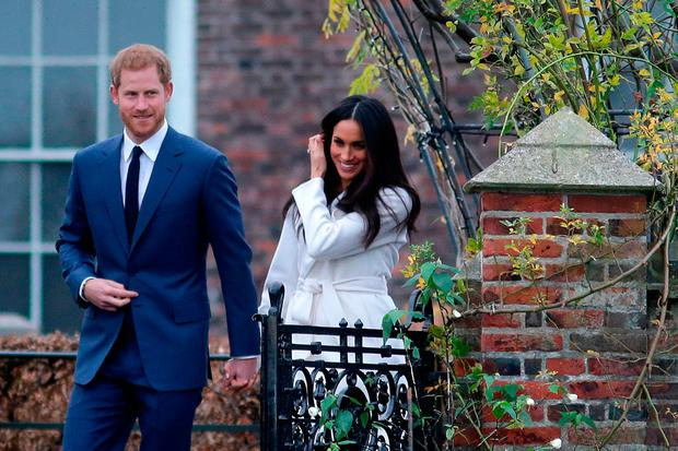 Britain's Prince Harry and his fiancée US actress Meghan Markle arrive to pose for photographs in the Sunken Garden at Kensington Palace in west London on November 27, 2017, following the announcement of their engagement