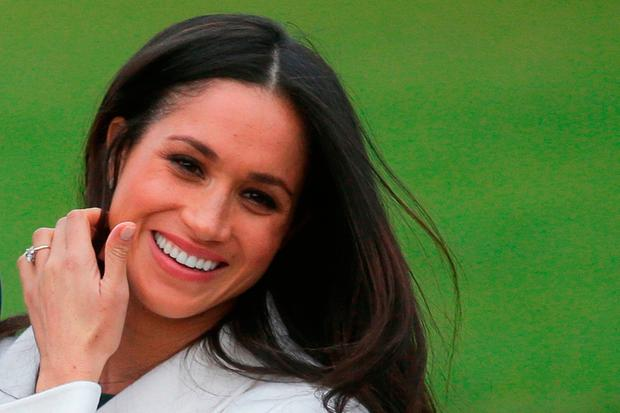 US actress Meghan Markle shows off her engagement ring she poses with her fiancée Britain's Prince Harry in the Sunken Garden at Kensington Palace in west London on November 27, 2017, following the announcement of their engagement