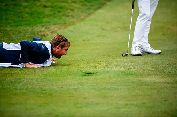 Matthew Fitzpatrick of England (R) stands as his caddie Jamie Lane looks at the green during round two of the Hong Kong Open at the Hong Kong Golf Club on November 24, 2017. / AFP PHOTO / Anthony WALLACE (Photo credit should read ANTHONY WALLACE/AFP/Getty Images)