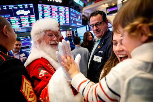 Hudson Maloney, son to specialist trader Gregg Maloney, is given a high five by Santa Claus, on the floor during the traditional bring-your-kids-to-work day at the New York Stock Exchange (NYSE)