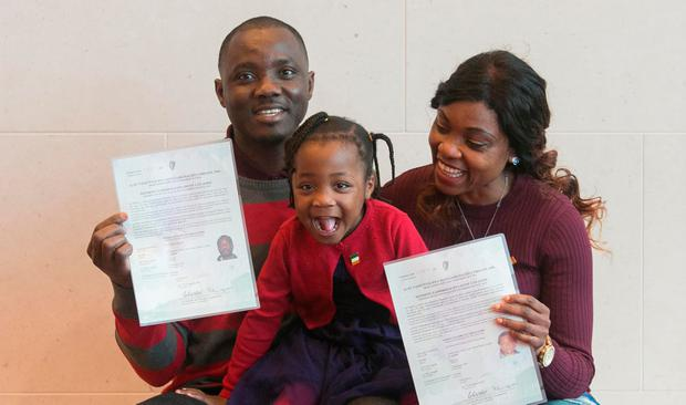 Pierre and Christine Kingne, originally from Cameroon but now living in Leixlip, Co Kildare, show their citizenship certificates to daughter Sinead (3) at the Convention Centre in Dublin. Photo: Gareth Chaney