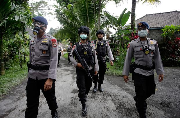 Police officers wear masks as they patrol in a village in Karangasem, Bali, Indonesia, Tuesday, Nov. 28, 2017. Indonesia authorities raised the alert for the rumbling volcano to highest level on Monday and closed the international airport on tourist island of Bali stranding thousands of travelers. (AP Photo/Firdia Lisnawati)