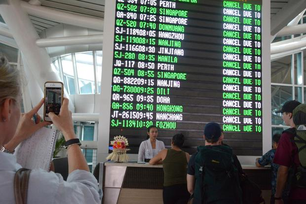 A flight information board shows cancelled flights at Ngurah Rai International Airport in Bali, Indonesia, Tuesday, Nov. 28, 2017. Indonesia's disaster mitigation agency says the airport on the tourist island of Bali is closed for a second day due to the threat from volcanic ash. (AP Photo/Ketut Nataan)