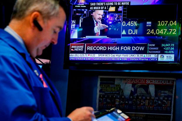 Traders work on the floor of the New York Stock Exchange, (NYSE) as a screen displays the Dow Jones Industrial Average as it crosses 24,000, in New York. Photo: Reuters