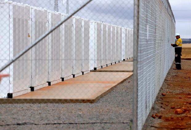 A worker checks the fence for the compound housing the Hornsdale Power Reserve, featuring the world's largest lithium ion battery made by Tesla, during the official launch near the South Australian town of Jamestown, in Australia, December 1, 2017. REUTERS/David Gray