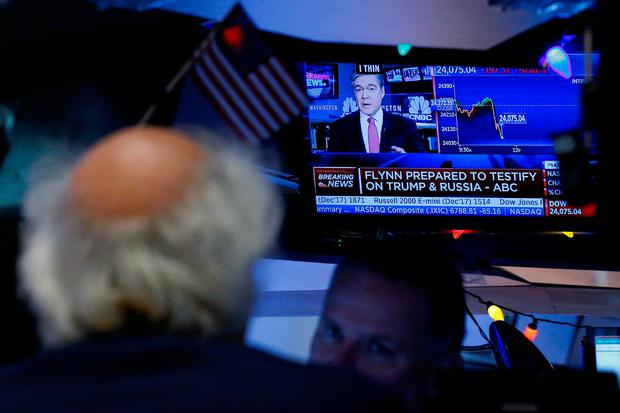 Traders watch, as a television displays the news about former US national security adviser Michael Flynn, at the New York Stock Exchange, (NYSE)