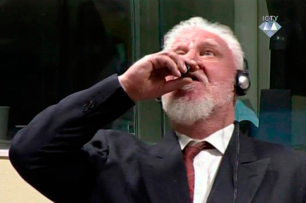 Slobodan Praljak brings a bottle to his lips. (ICTY via AP)