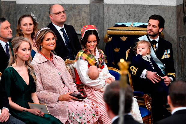 (L-R) Sara Hellqvist (sister of Princess Sofia), princess Madeleine, princess Sofia holding baby prince Gabriel and prince Carl Philip with prince Alexander sit during prince Gabriel's christening in Drottningholm Palace Chapel outside Stockholm, on December 1, 2017