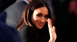 US actress Meghan Markle waves as she leaves with Prince Harry (not seen) after watching a hip hop opera performed by young people involved in the Full Effect programme at the Nottingham Academy school on December 1, 2017 in Nottingham, England
