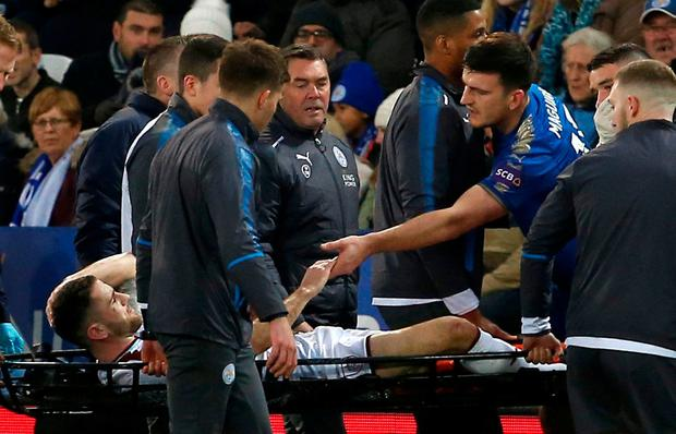 Leicester City's Harry Maguire shakes hands with Burnley's Robbie Brady as he is stretchered off after they collided