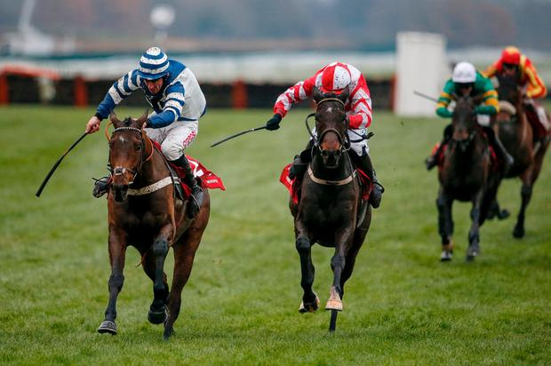 Paul Townend riding Total Recall (C, red) clears the last to win The Ladbrokes Trophy Steeple Chase from Whisper (L) at Newbury