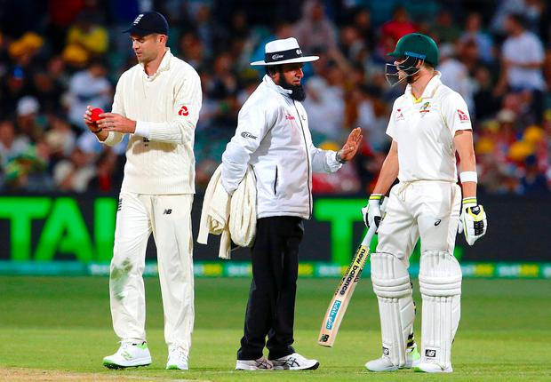 Umpire Aleem Dar stands between England's James Anderson and Australia's captain Steve Smith during the first day of the second Ashes cricket test match. Photo: David Gray/Reuters