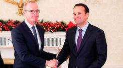 Taoiseach Leo Varadkar (right) shakes hands with the newly appointed Tanaiste Simon Coveney at the Aras in Dublin Photo: Brian Lawless/PA Wire