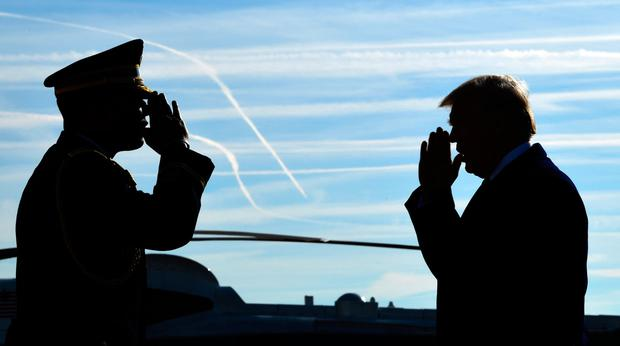 Hail to the chief: President Donald Trump is greeted with a salute as he walks down the steps of Air Force One at John F. Kennedy International Airport in New York on his return to his home city yesterday to attend a series of fundraisers Photo: AP Photo/Susan Walsh