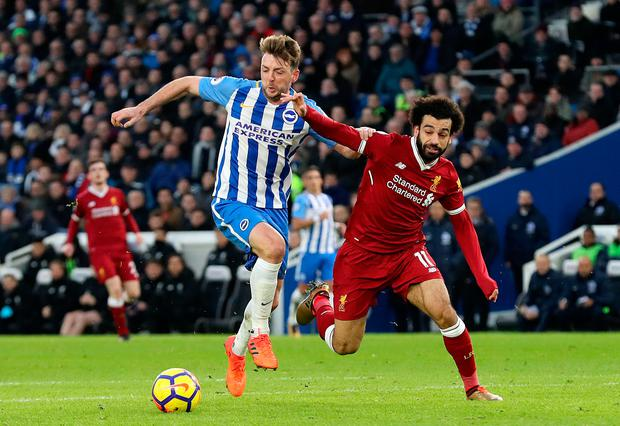 Brighton & Hove Albion's Dale Stephens and Liverpool's Mohamed Salah tussle for possession. Photo: PA