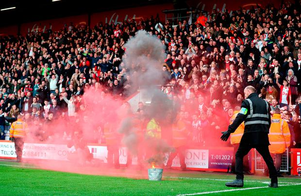 A flare is extinguished on the sideline at the Vitality Stadium. Photo: PA