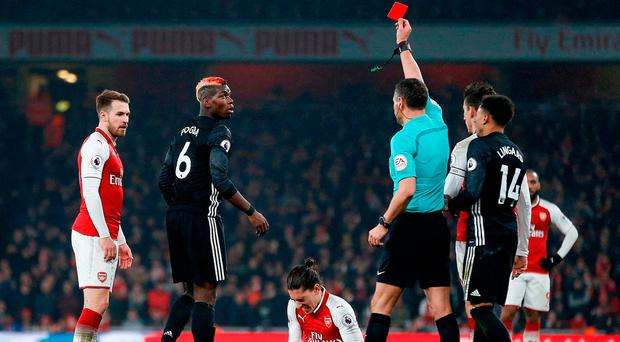 Andre Marriner shows a red card to Manchester United's Paul Pogba for his challenge on Hector Bellerin. Photo: AFP/Getty Images