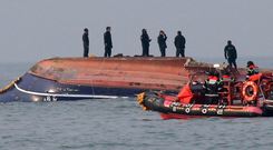South Korean Coast Guard officers stand aboard the upturned hull of the fishing boat which collided with a refuelling vessel in the waters off Incheon, South Korea Photo: South Korea Ongjin County via AP