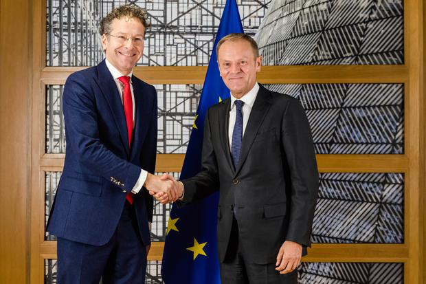 European Council President Donald Tusk, right, shakes hands with the chair of the Eurogroup Jeroen Dijsselbloem ahead of a meeting of eurozone finance ministers at the Europa building in Brussels on Monday, Dec. 4, 2017. (AP Photo/Geert Vanden Wijngaert)