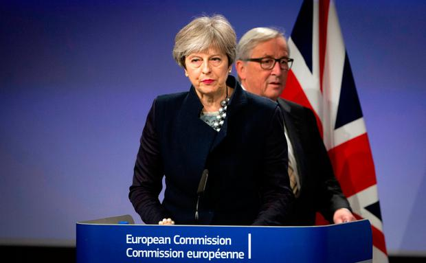 European Commission President Jean-Claude Juncker, right, walks behind British Prime Minister Theresa May prior to addressing a media conference at EU headquarters in Brussels. Photo: AP