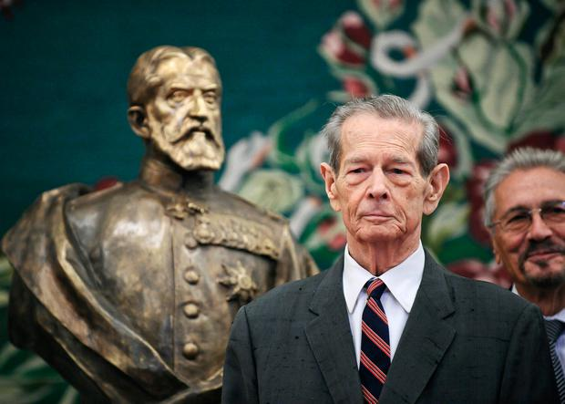 Former Romanian King Michael poses next to a bronze sculpture depicting the founder of Romania's royal dynasty, King Carol I, in the country's parliament in Bucharest, Romania (AP Photo/Octav Ganea, File)