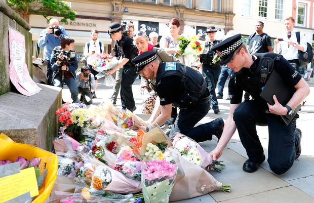 File photo dated 23/05/17 of police officers laying flowers in St Ann's Square, Manchester, the day after a suicide bomber killed 22 people, including children, as an explosion tore through fans leaving a pop concert in Manchester. Peter Byrne/PA Wire