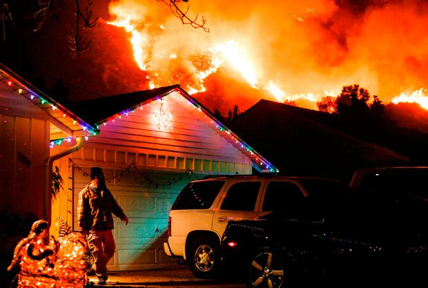 A man prepares to evacuate his home as a wildfire burns along a hillside near homes in Santa Paula, California. Photo: Getty Images
