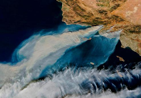 This image obtained from NASA Earth Observatory, shows smoke from the Thomas Fire (top C) in California blowing out to the Pacific Ocean on December 5, 2017, along with smoke from the Creek and Rye fires (top R). A thousand firefighters were battling the wind-whipped brush fires in southern California on Tuesday that has left at least one person dead, sent thousands fleeing, and destroyed more than 150 homes and businesses. / AFP PHOTO / NASA Earth Observatory / HO