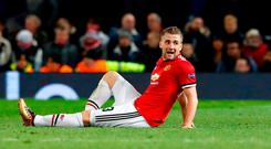 Manchester United's Luke Shaw sits on the pitch with cramp during the UEFA Champions League match at Old Trafford