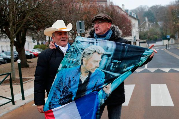 French fans Andre Thibert, left, and Andre Duval pay tribute with a poster of the late rock star while walking to his house in Marnesla-Coquette, outside Paris, yesterday. Photo: AP