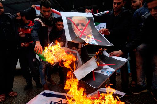 Palestinians burn posters depicting Donald Trump and Benjamin Netanyahu during a protest in Rafah in the southern Gaza Strip. Photo: Reuters