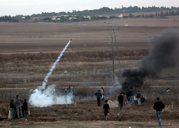 A Palestinian protester throws back a teargas canister that was fired by Israeli soldiers during clashes on the Israeli border with Gaza, Thursday, Dec. 7, 2017. (AP Photo/ Khalil Hamra)