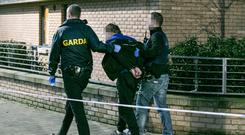 A man is led from the scene in handcuffs by gardaí