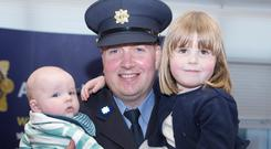 Garda Sgt Diarmuid O'Donovan, from Leixlip, Co Kildare, with his children Ross (5 months) and April (4) after he was awarded a Silver Scott Medal for bravery at the passing-out ceremony in Templemore. Photos: Liam Burke/Press 22