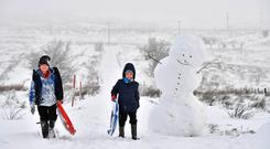 Children off from school due to the weather make their way past a large snowman on Black mountain on December 8, 2017 in Belfast, Northern Ireland. (Photo by Charles McQuillan/Getty Images)