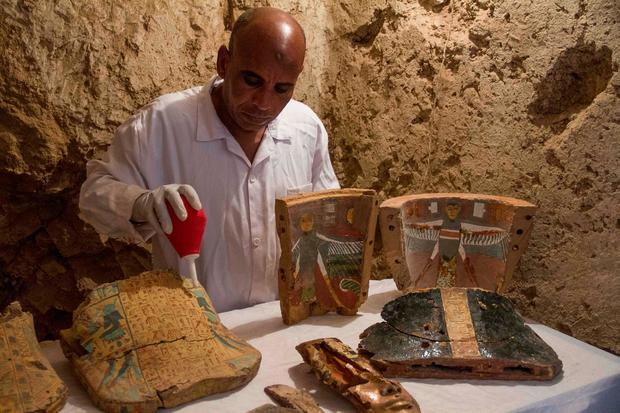 PRICELESS: An Egyptian archaeologist with funeral furniture found in a newly discovered tomb on Luxor's West Bank. Photo: AP