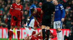 Liverpool's Jordan Henderson holds his leg as Everton's Wayne Rooney speaks to referee Craig Pawson