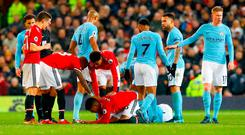 Players gather round Manchester United's Marcos Rojo as he sits on the ground injured