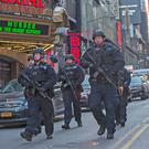 Heavily armed police patrol the scene of a terrorist attack near the Port Authority bus terminal in New York. Photo: Mark Condren