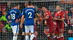 Liverpool's Croatian defender Dejan Lovren (2R) remonstrates with referee Craig Pawson (C obscured) after Lovren conceded a penalty during the English Premier League football match between Liverpool and Everton at Anfield in Liverpool, north west England on December 10, 2017. / AFP PHOTO / Paul ELLIS