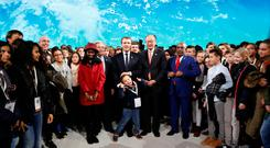 French President Emmanuel Macron (C), World Bank President Jim Yong Kim (CenterR), and President of the Comores, Azali Assoumani (4thR), pose with children after the closing speech of the Plenary Session of the One Planet Summit at the Seine Musicale event site on the Ile Seguin in Boulogne-Billancourt, near Paris, France, December 12, 2017. REUTERS/Etienne Laurent/Pool