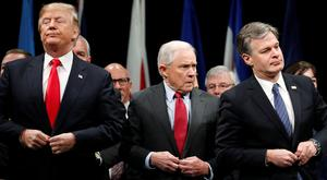 US President Donald Trump, Attorney General Jeff Sessions and FBI Director Christopher Wray button their coats as they stand for the national anthem at a graduation ceremony at the FBI Academy in Quantico, Virginia. Photo: Reuters