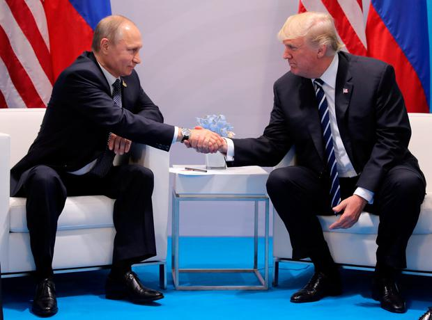 Donald Trump shakes hands with Vladimir Putin during a meeting earlier this year Photo: REUTERS/Carlos Barria